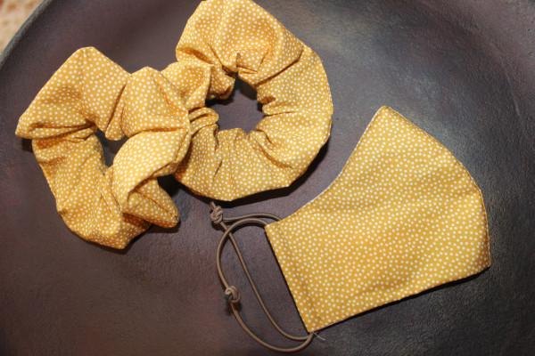 Senffarbene Behelfsmaske mit kleinen, weißen Punkten