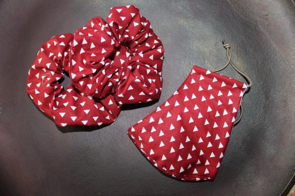 Rote Behelfsmaske mit kleinen, weißen Dreiecken